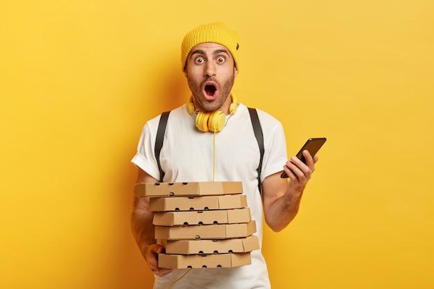 Fattorino stupito riceve ordini dai clienti tramite smartphone, tiene una pila di scatole di cartone per pizza, trasporta lo zaino, indossa cappello e maglietta, isolato su sfondo giallo, lavora in ristorante Foto Gratuite