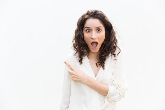 Amazed excited woman with open mouth pointing finger away Free Photo