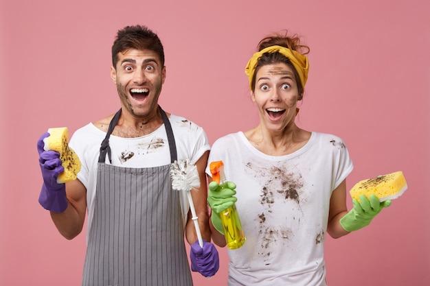 汚れた服と顔をした驚きの女性と男性は、非常に迅速に仕事を終えるために嬉しいことに驚いています。陽気な女性がスポンジを保持し、スプレーと彼女の夫をブラシとスポンジで洗う 無料写真