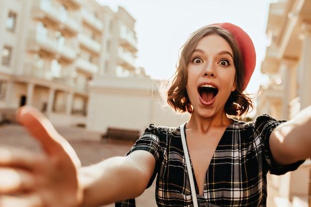 Signora francese stupita con gli occhi marroni che fanno selfie sulla strada. ragazza riccia divertente in berretto rosso che cattura maschera di se stessa mentre cammina per la città. Foto Gratuite