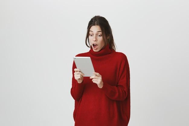 Lo sguardo stupito della ragazza all'esposizione digitale della compressa ha colpito Foto Gratuite