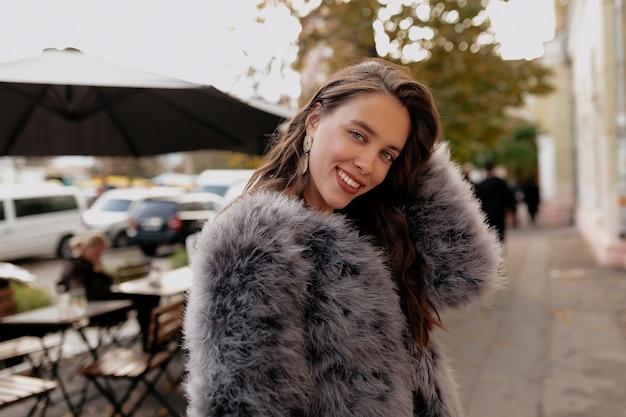 긴 검은 머리가 그녀의 머리를 만지고 따뜻한 날에 카메라에 웃고 놀란 아가씨. 무료 사진