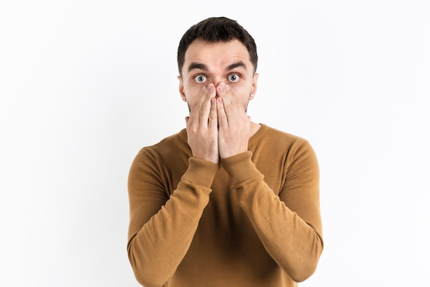 Amazed man covering mouth with hands Free Photo
