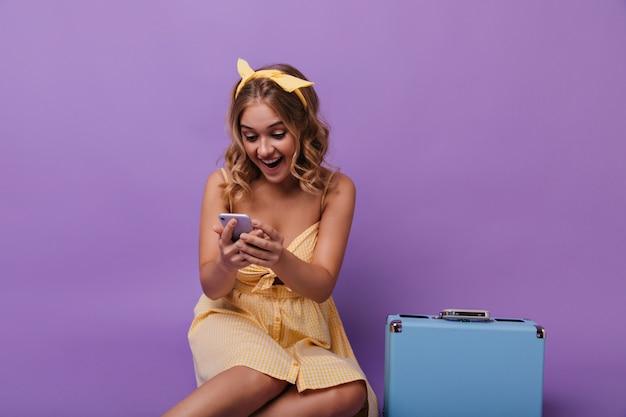 Bella ragazza stupita con la valigia leggendo il messaggio telefonico. ritratto di gioiosa signora riccia con valigia blu guardando il suo smartphone. Foto Gratuite