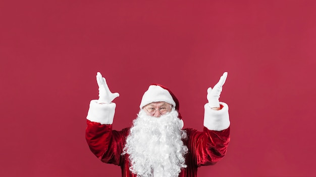 Amazed santa claus in hat with hands up Free Photo