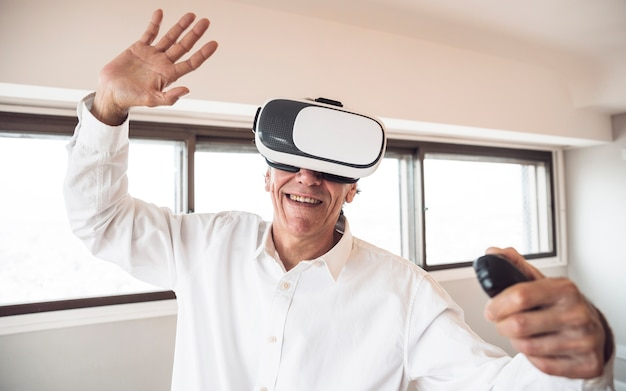 Amazed senior man touching in the air during the vr experience Free Photo