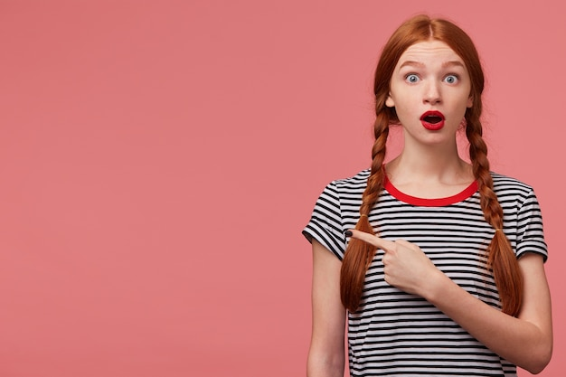Пораженная потрясенная взволнованная девочка-подросток с двумя рыжими косичками красная помада с открытым ртом в панике, указывая пальцем на левую сторону, привлекает ваше внимание, чтобы скопировать пространство, обеспокоенная озадаченная розовая стена Бесплатные Фотографии