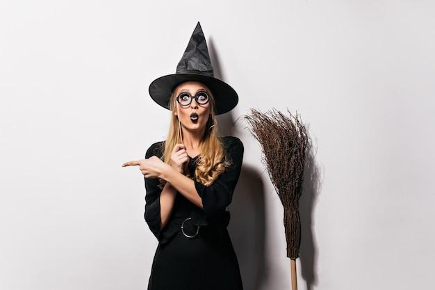 Пораженный волшебник в очках, стоя на белой стене. смешная эмоциональная ведьма позирует со шляпой и метлой. Бесплатные Фотографии