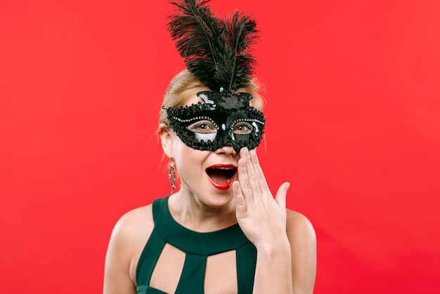 Amazed woman in black carnival mask Free Photo