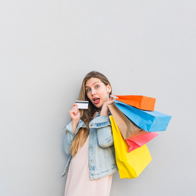 Amazed woman standing with shopping bags and credit card at light wall Free Photo