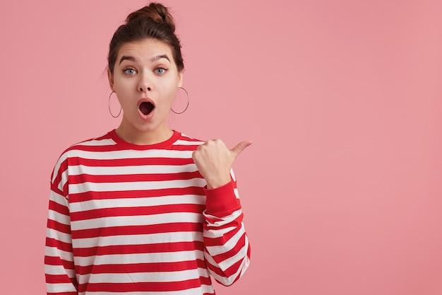 Изумленная юная самка с веснушками носит полосатый лонгслив; широко открывает рот от волнения, отвисшая челюсть, привлекает внимание, изолирована на розовой стене Бесплатные Фотографии