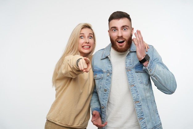 Amazed young pretty couple raising emotionally their hands while looking surprisedly with wide eyes opened, standing on white Free Photo