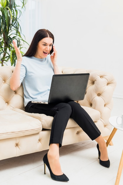 Amazed young woman sitting on couch with laptop and talking by phone Free Photo