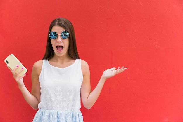 Amazed young woman with smartphone Free Photo