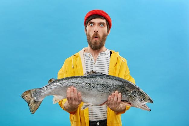 놀라움과 의외 성 개념. 멍청한 눈과 턱으로 보이는 굵은 수염을 가진 충격에 휩싸인 젊은 어부는 자신이 잡을 수 있다고 믿지 않는 거대한 물고기를 안고 떨어졌습니다. 무료 사진