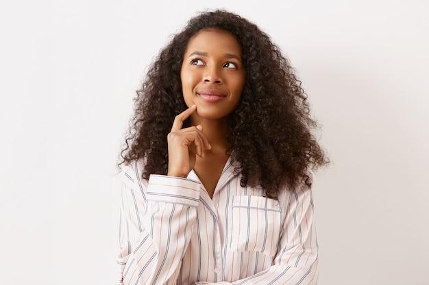 夢のような物思いにふける表情を持ち、見上げて笑い、人差し指をあごにかざし、休暇の計画とエキサイティングな未来を考えているアフリカ系アメリカ人出身の驚くべき愛らしい女の子 無料写真
