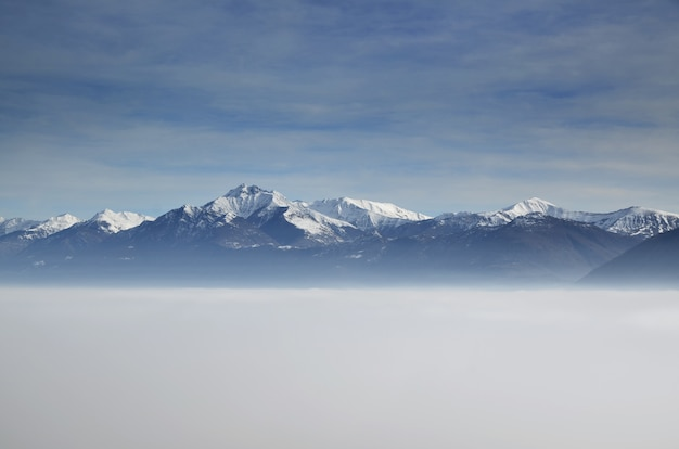 Amazing aerial view of mountains partially covered with snow and positioned higher than clouds Free Photo