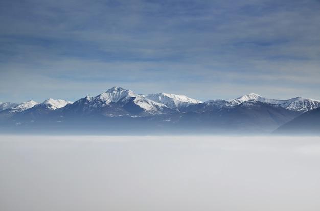 部分的に雪に覆われ、雲よりも高い位置にある山々の素晴らしい空中写真 無料写真