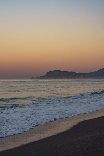 끝없는 수평선과 외로운 산이 멀리 떨어진 놀라운 해변 일몰 무료 사진