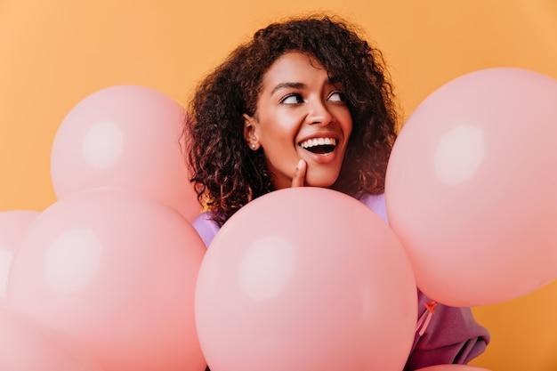 오렌지에 포즈 파티 풍선 놀라운 흑인 여성 모델. 이벤트 기간 동안 재미 사랑스러운 갈색 머리 여자. 무료 사진