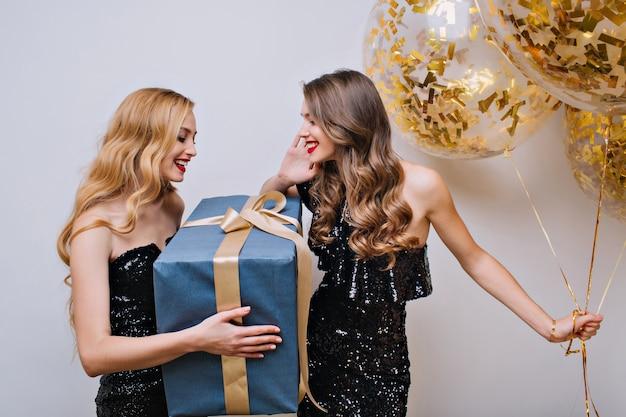 놀라운 금발 소녀는 밝은 갈색 머리를 가진 여자 친구로부터 큰 선물을 받았습니다. 파티 풍선을 들고 갈색 자매를위한 선물을 들고 매력적인 젊은 여자의 실내 초상화. 무료 사진