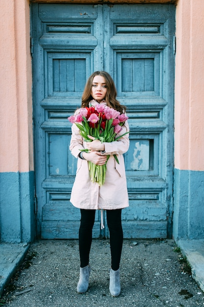 Amazing brunette woman standing in front of old  blue door with a bouquet of tulips. Premium Photo
