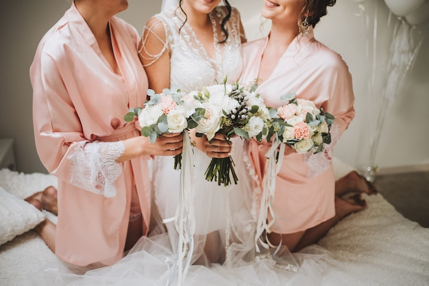 Amazing caucasian bride with her lovely bridesmaids holding bouquets in the morning of the wedding Premium Photo