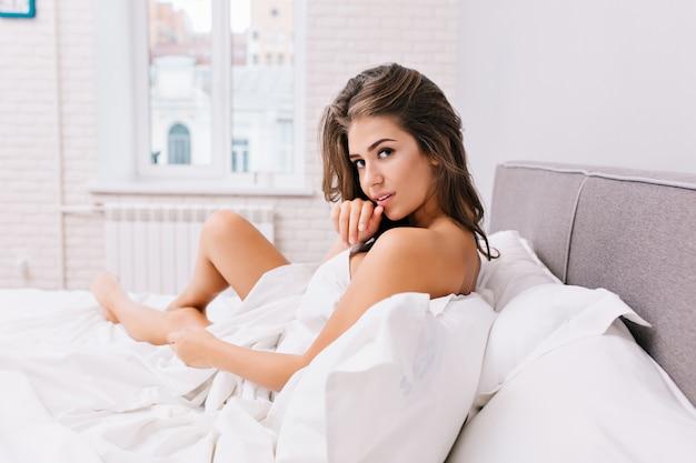 Удивительная очаровательная девушка с длинными волосами брюнетки отдыхает в белой кровати в современной квартире. сексуальный вид, положительные эмоции, утреннее пробуждение, хорошее настроение, красивая модель. Бесплатные Фотографии