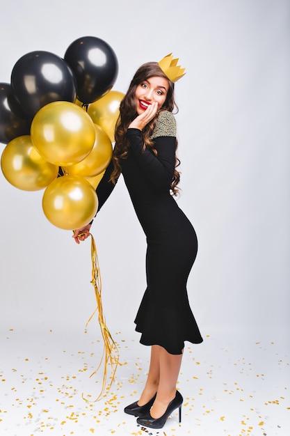 Incredibile donna alla moda allegra in abito da sera nero di lusso e corona gialla sulla testa per celebrare il nuovo anno, sorridente e con palloncini gialli e neri, labbra rosse, faccia sorpresa di emozione. Foto Gratuite