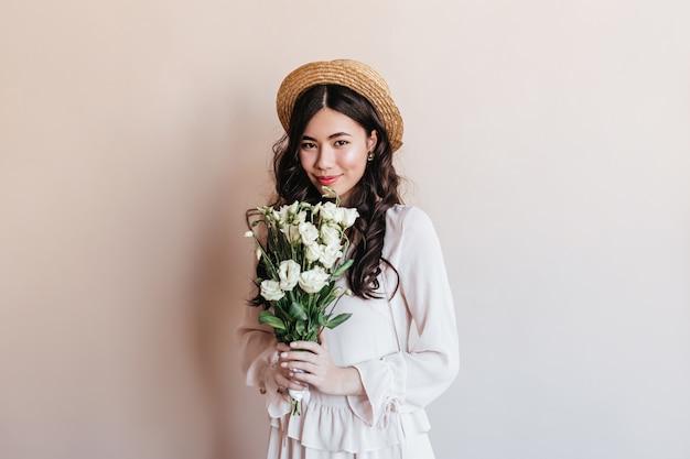 トルコギキョウの花を保持している驚くべき巻き毛の日本人女性。ブーケと恥ずかしがり屋のアジアの女性のスタジオショット。 無料写真