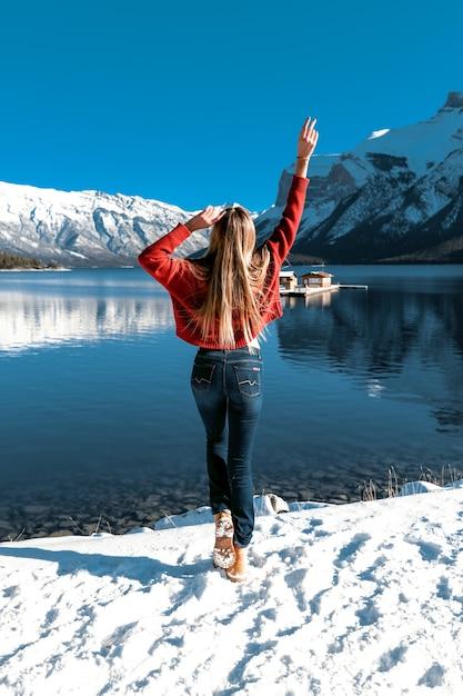 一人でアウトドアを楽しんでいる素晴らしい女の子は、完璧な自然の景色を楽しんでいます。青い澄んだ空、大きな山と湖。冬の寒さ。暖かいニットの赤いセーターとスキニージーンズ。 無料写真