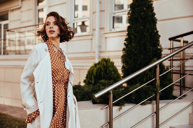 目をそらしている長い白衣の素晴らしい女の子。通りに立っている快活な官能的な女性の屋外ショット。 無料写真