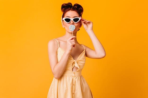 롤리팝을 핥는 선글라스에 놀라운 소녀. 노란 공간에 고립 된 생강 핀 업 여자의 스튜디오 샷. 무료 사진