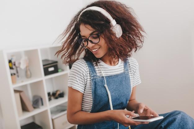 어두운 갈색 곱슬 머리가 흰색 이어폰에서 사무실 듣는 음악에서 재미를 가진 놀라운 소녀 무료 사진