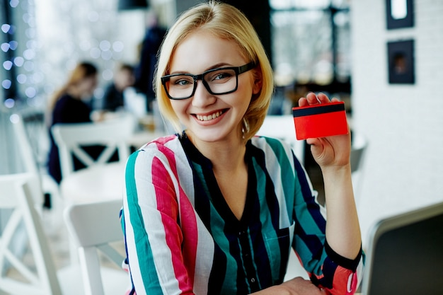 Amazing girl with light hair wearing colorful shirt and glasses sitting in cafe with laptop and credit card, freelance concept, online shopping, smiling. Premium Photo