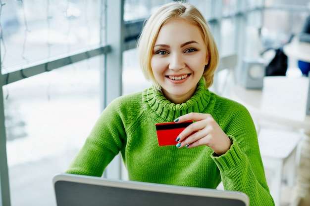Amazing girl with light hair wearing green sweater sitting in cafe with laptop and credit card, portrait, freelance concept, online shopping. Premium Photo
