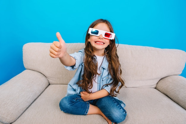Удивительная счастливая маленькая девочка в очках 3d с длинными волосами брюнет, улыбаясь в камеру на диване, изолированном на синем фоне. проявление настоящих положительных эмоций, счастливого детства модного малыша Бесплатные Фотографии