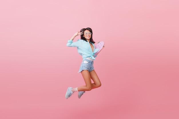 Incredibile ragazza alla moda latina in abito da strada che salta con lo skateboard. donna alla moda in pantaloncini di jeans e calzini a righe divertendosi Foto Gratuite