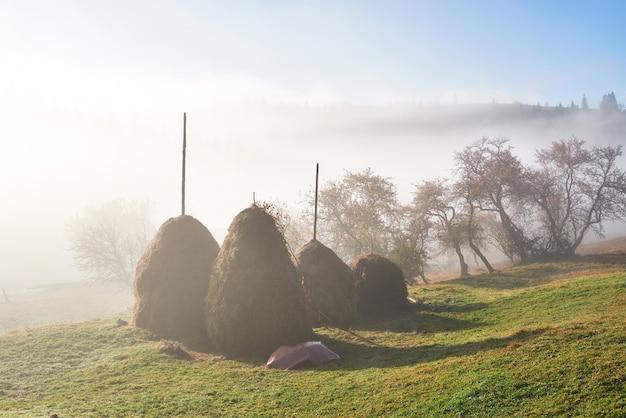秋の霧と干し草の山と素晴らしい山の風景 無料写真