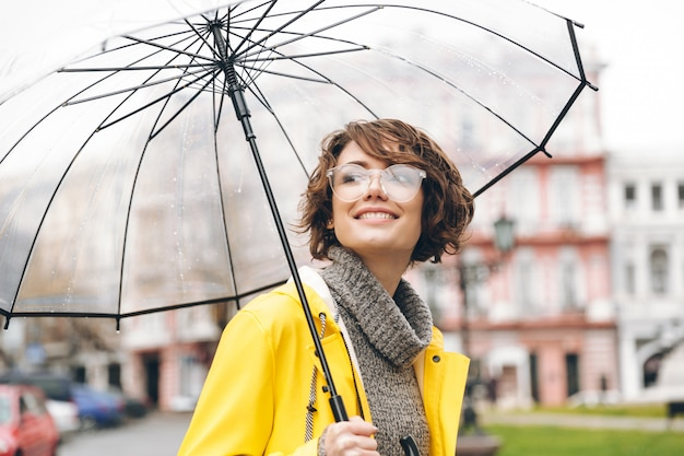 Amazing portrait of happy woman in yellow raincoat walking in city under transparent umbrella during cold rainy day Free Photo