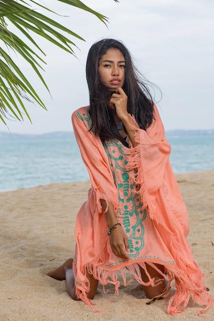 Incredibile donna asiatica abbronzatura sexy in posa sulla spiaggia tropicale paradiso sotto l'albero di pam, seduto sulla sabbia bianca, rilassarsi e godersi le vacanze. abito boho con ricami. bali. Foto Gratuite