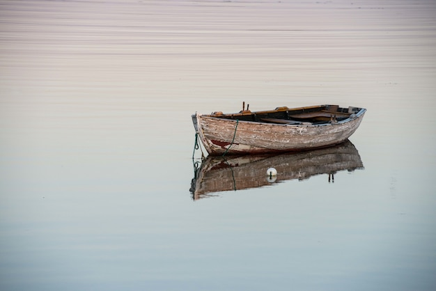 反射する湖の上の古い木製のボートの素晴らしいショット 無料写真