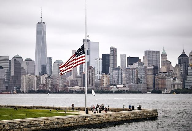 マンハッタンのスカイラインの背景にある公園での米国旗の素晴らしいショット 無料写真