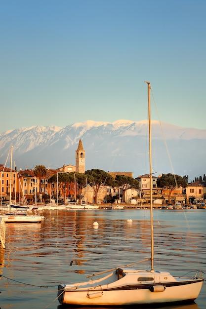 Amazing of sunset on lake garda, italy. yachts and harbor Premium Photo