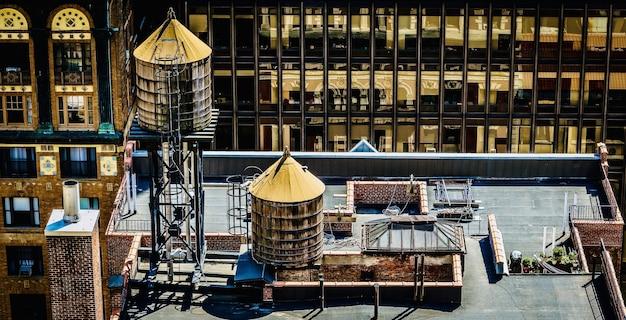 물 탱크가있는 시내 건물 지붕의 놀라운 전망 무료 사진