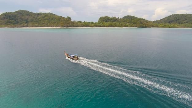 Удивительный вид на лодку, плывущую в открытом море в ветреный день. взгляд дрона - угол глаз птицы. - увеличьте цвет обработки. Premium Фотографии