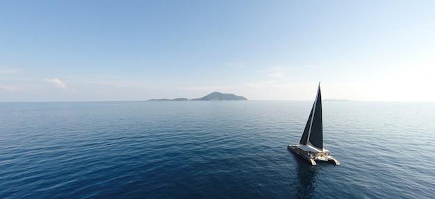 Удивительный вид на яхту, парусную в открытом море в ветреный день. взгляд дрона - угол глаз птицы. - увеличьте цвет обработки. Premium Фотографии