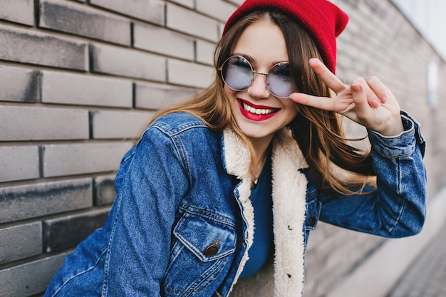 Incredibile ragazza bianca in occhiali rotondi alla moda in posa con il segno di pace. colpo esterno di donna bruna intelligente che ride nel muro di mattoni di sfocatura. Foto Gratuite