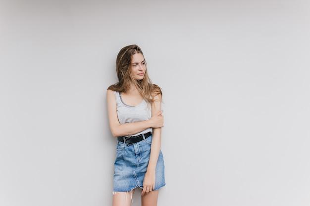 Удивительная женщина в джинсовой юбке позирует в белой стене. крытый выстрел симпатичной девушки брюнетки изолированной с задумчивым выражением лица. Бесплатные Фотографии