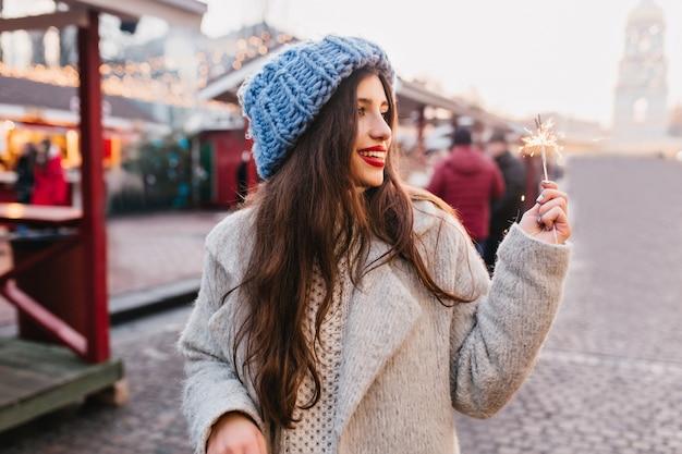 灰色のコートと線香花火で通りを歩いて青い帽子の素晴らしい女性。屋外の時間を費やして笑顔でベンガルの光を見て冬の服装で愛らしい女性。 無料写真
